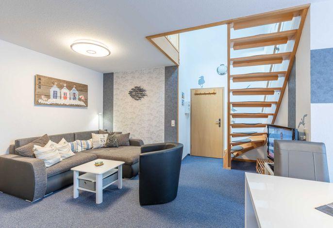 Wohnzimmer mit Sofa und Treppe zur Galerie mit den Betten