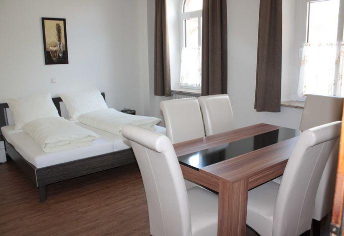 Ferienwohnung EG: Wohn- und Schlafzimmer mit Esstisch, TV und Doppelbett