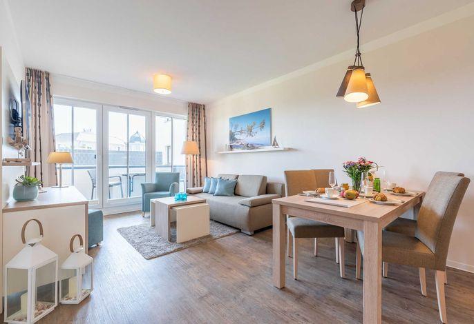 Wohn/Essbereich mit Couch, Esstisch und Zugang zum Balkon
