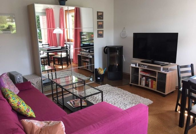 Wohnzimmer mit Kaminofen, Couch mit Couchtisch, Schrank und Flachbild-TV