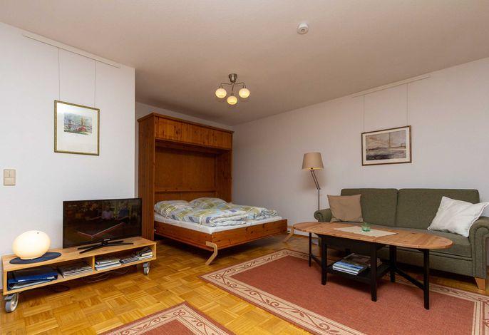 Wohnzimmer mit aufgeklappten Bett