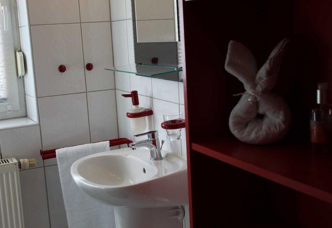 Das Bad mit dem Waschbecken zu sehen und dem Regal.