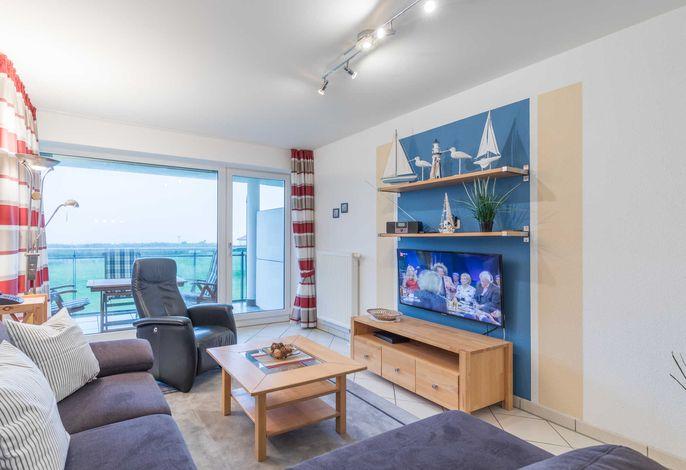 Wohnzimmer mit gemütlicher Sitzecke, TV und Zugang zum Balkon mit Seesicht