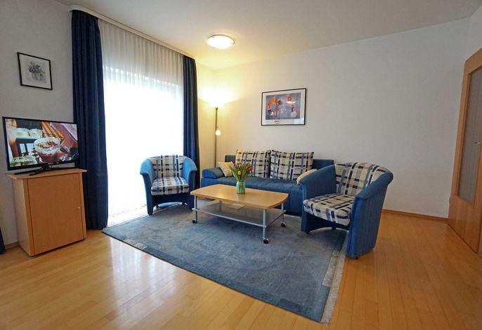 Wohnzimmer mit Flachbildfernseher und Schlafcouch