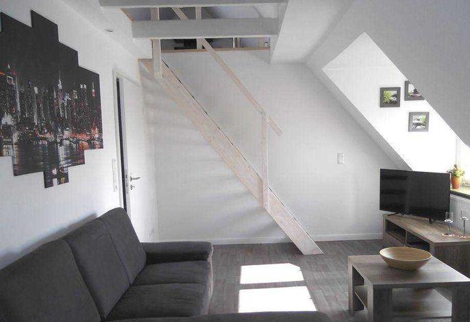 Wohnzimmer mit Zugang über eine Treppe zur offenen Galerie