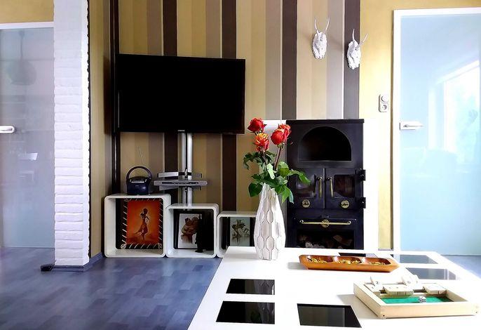 Das gemütliche Wohnzimmer: Der Blick vom Sofa auf TV und Kaminofen