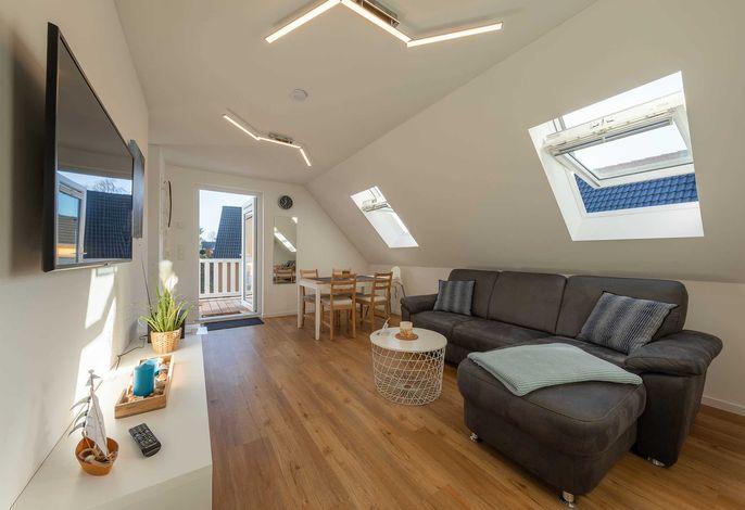 Heller Wohnbereich mit Flachbild TV in der Ferienwohnung Merlin Ausguck