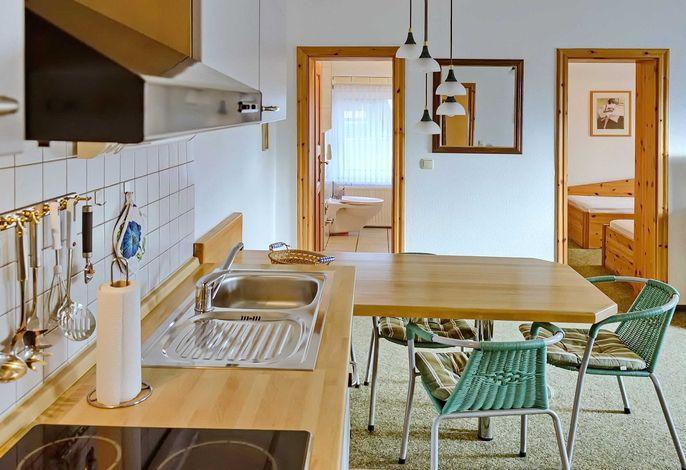 Blick vom Schlafzimmer mit Doppelbett zur Küchenzeile mit Essbereich
