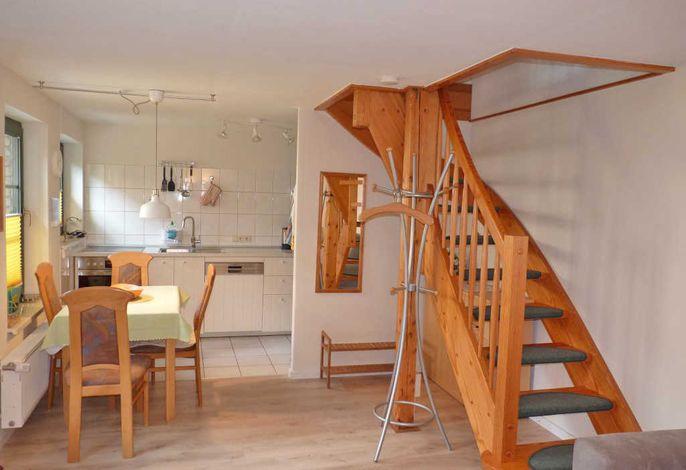 offene Küche mit Sitzgruppe und Treppe zum Schlafraum Ferienhaus