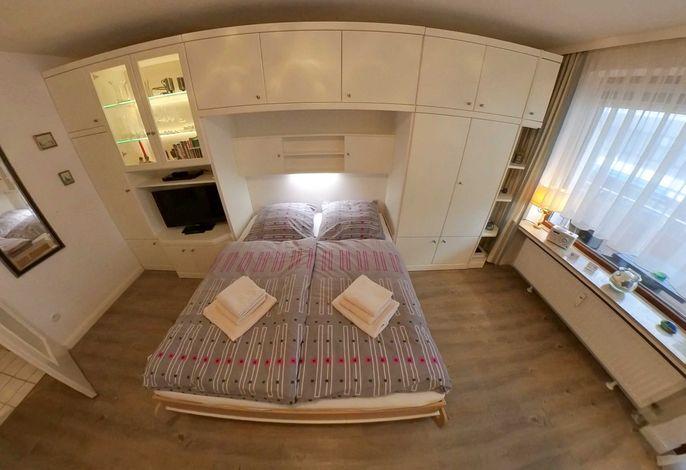 Blick auf Bett und Schrankwand mit Fernseher.