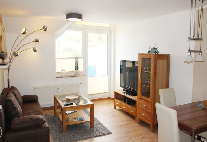 Wohnzimmer mit offener Küchenzeile, Schlafcouch, Couchtisch, Schrank sowie Flachbild-TV