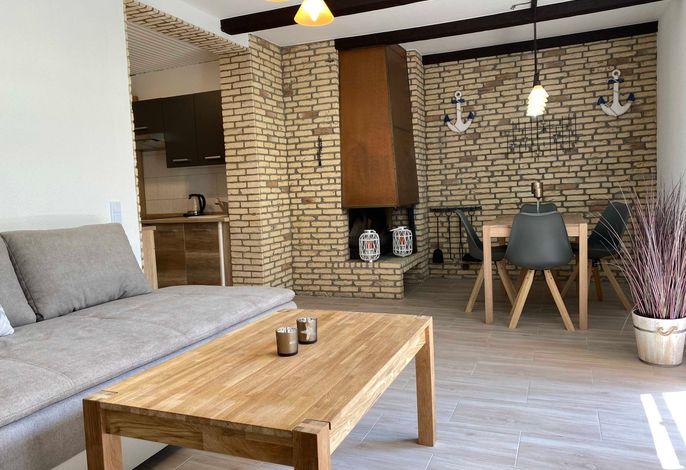 Wohnraum mit Essbereich, offenem Kamin und Zugang zur Küche