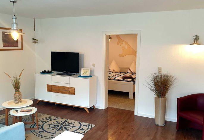 Blick vom Wohnraum mit Couch, Flach-TV und Leseecke in das Schlafzimmer
