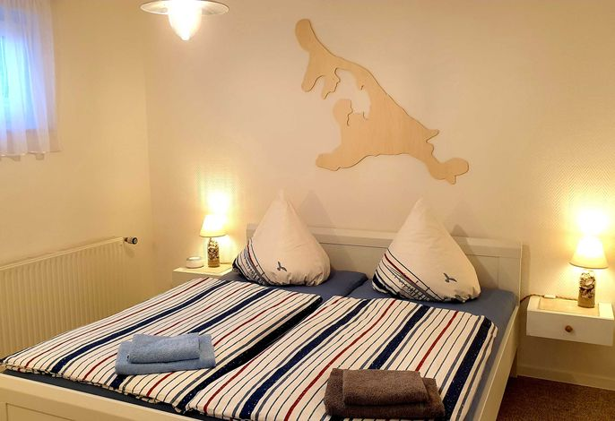 Schlafzimmer mit Doppelbett und Kleiderschrank