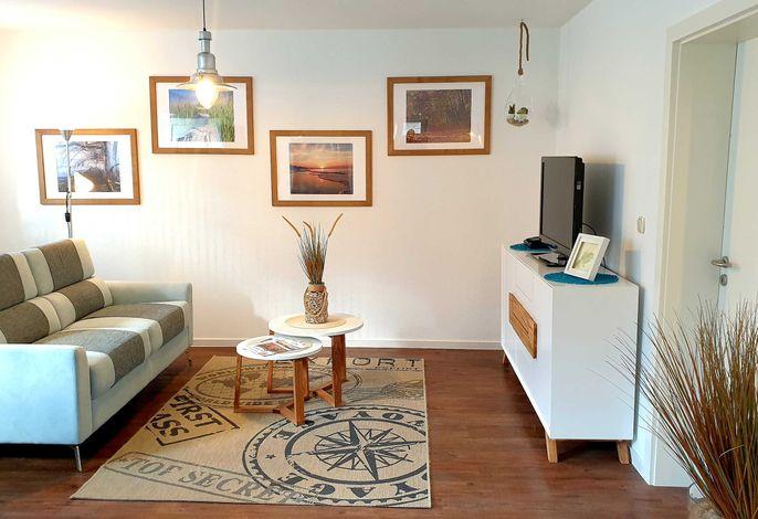 Wohnraum mit Couch, Flach-TV und Leseecke