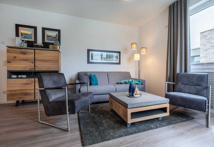 Wohnbereich mit Doppelschlafcouch und Couchtisch