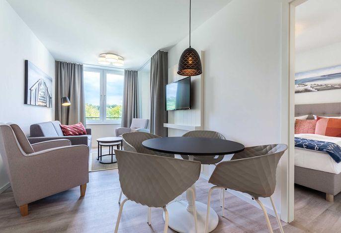 Wohn-/Essbereich mit Sitzgelegenheit und Zugang zum Schlafzimmer