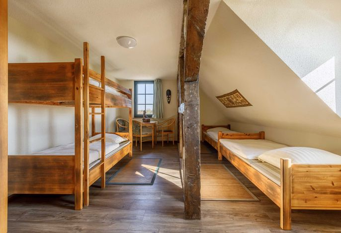 Beispielsbild. Das Zimmer ist im gleichen Design, hat die gleiche Ausstattung, jedoch mit Doppelbett, Etagenbett und einer gemütlichen Sitzgruppe.
