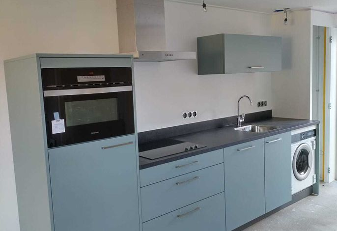 Neue Küche mit Geschirrspüler und Waschmaschine im Wohnzimmer