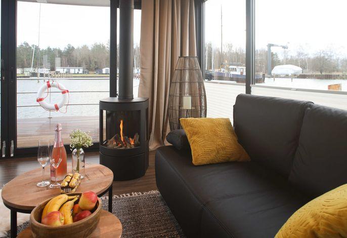 Zimmerbeispiel Wohnbereich mit Kamin und Rundumblick auf den Hafen