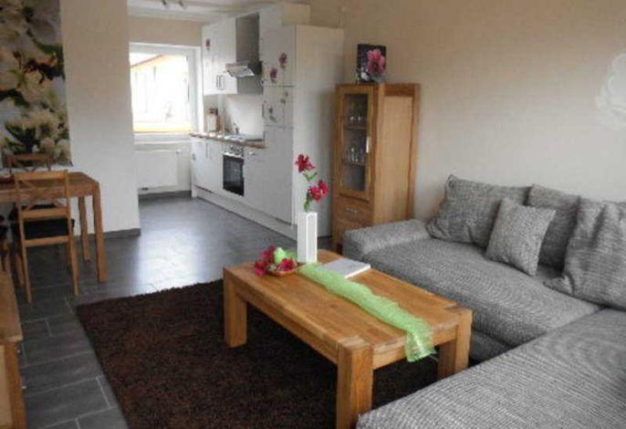 Wohnbereich mit großer Couch und Blick auf die Küche