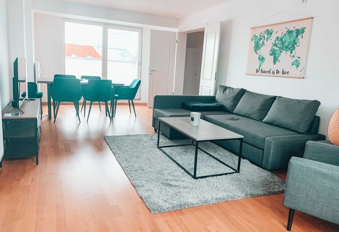 Wohnzimmer mit Esstisch und gemütlicher Schlafcouch