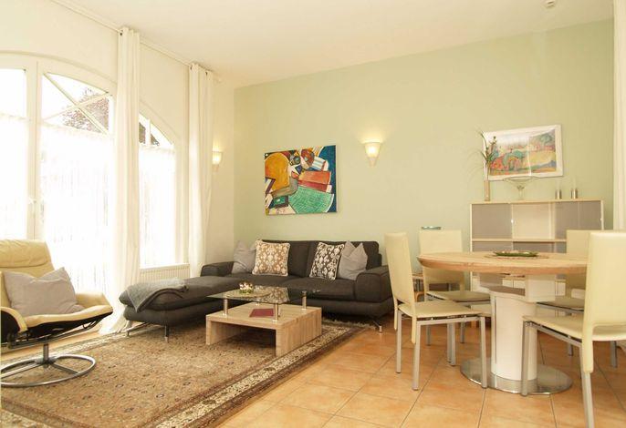 Der Wohnbereich mit Couchgarnitur, Sitzecke und Zugang zur Terrasse