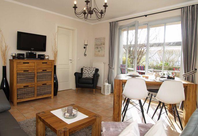 das gemütliche Wohnzimmer mit Essecke, Flachbild-TV und Zugang zur Terrasse