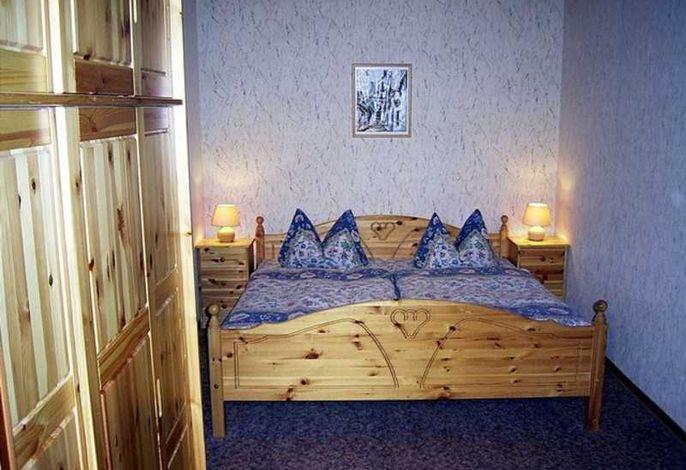 Schlafzimmer mit Doppelbett und geräumigem Kleiderschrank