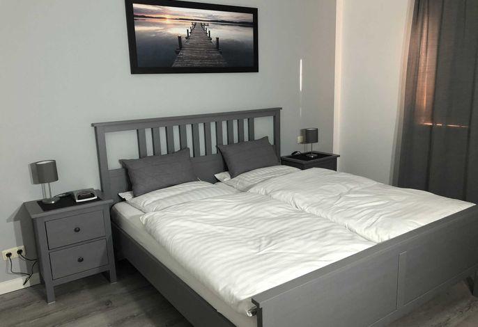 Geräumiges Zweiraumappartement, Schlafzimmer mit Doppelbett.