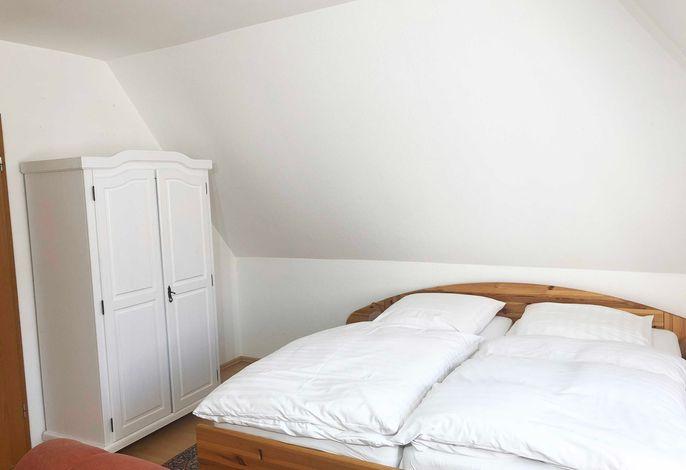 großes Doppelbett im Wohn-Schlafzimmer