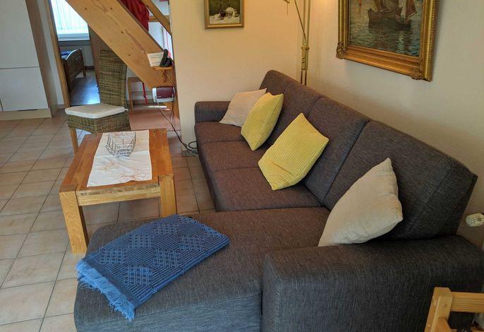 Sofa im Wohnzimmer mit Essecke und offener Küche