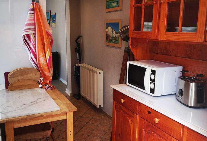 Von der überdachten Terrasse gehen Sie duch die Küche ins Wohnzimmer.