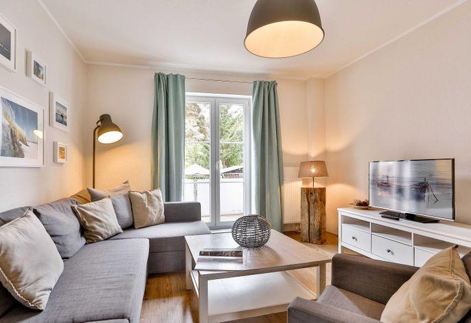 Wohnbereich mit TV, gemütlicher Couch-Ecke und Zugang zum Balkon