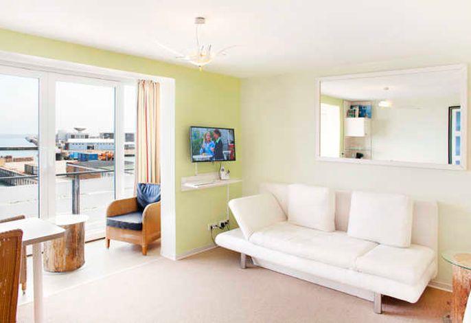 Das helle Zimmer ist mit einem TV, einem Sitzbereich und einem eigenen Bad ausgestattet