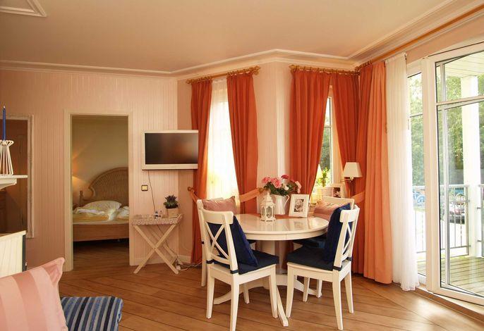 Der Wohnbereich mit Essecke und Flachbild-TV sowie einem Zugang zum Balkon mit Meerblick