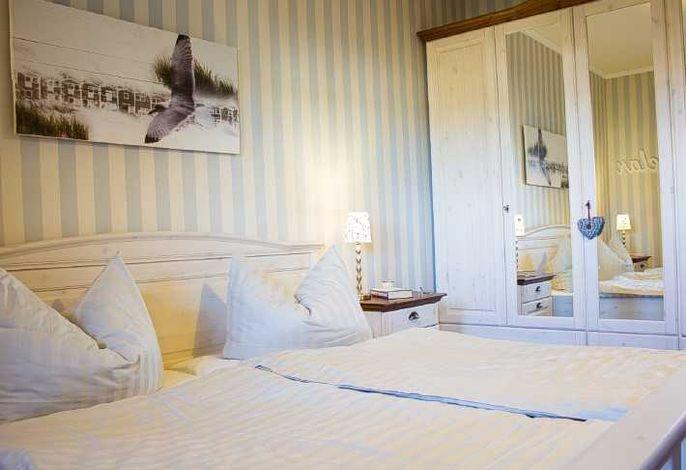 Das Schlafzimmer mit Doppelbett und großem Kleiderschrank