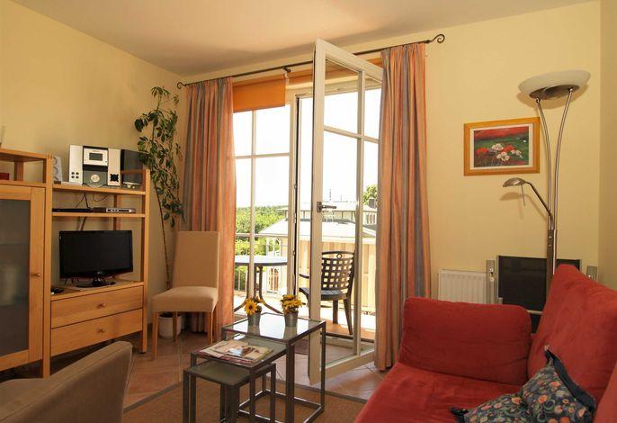Das Wohnzimmer mit Zugang zum möblierten Balkon