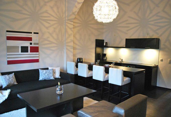 Wohnraum mit Sitzecke, TV und offener Küche