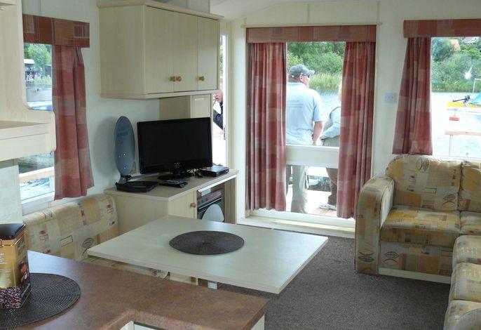 Wohnraum mit Tisch, Sitzecke und TV