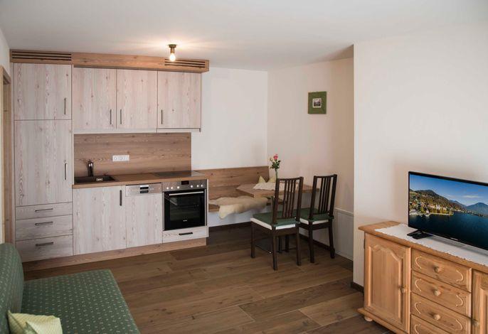 gemütliche Wohnküche mit gut ausgestatteter Küchenzeile, Sitzecke und Couch