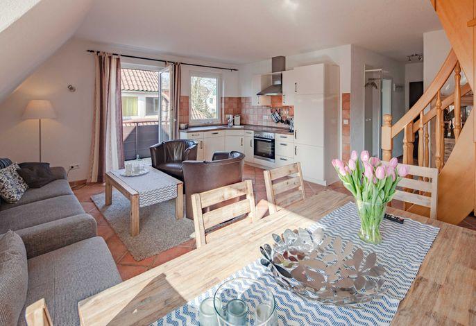 Wohnbereich mit offener Küche und Zugang zum Balkon