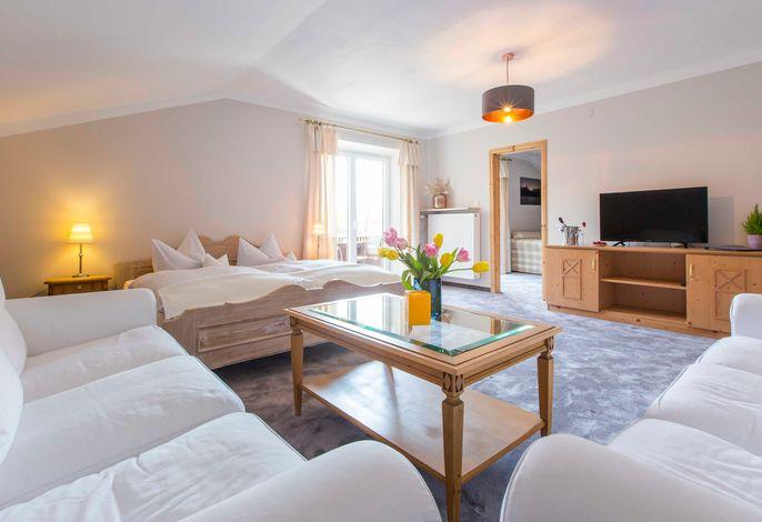 Wohnzimmer mit Couchen und Doppelbett