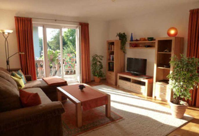 Blick in unser Wohnzimmer mit Sofa und TV mit Zugang zum Westbalkon