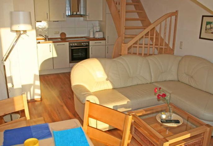 Offener Wohnbereich mit Küchenzeile und Aufgang zum Schlafbereich.