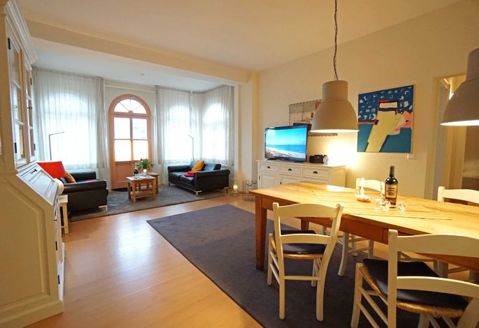 Wohnzimmer mit Esstisch, Sitzecke und TV