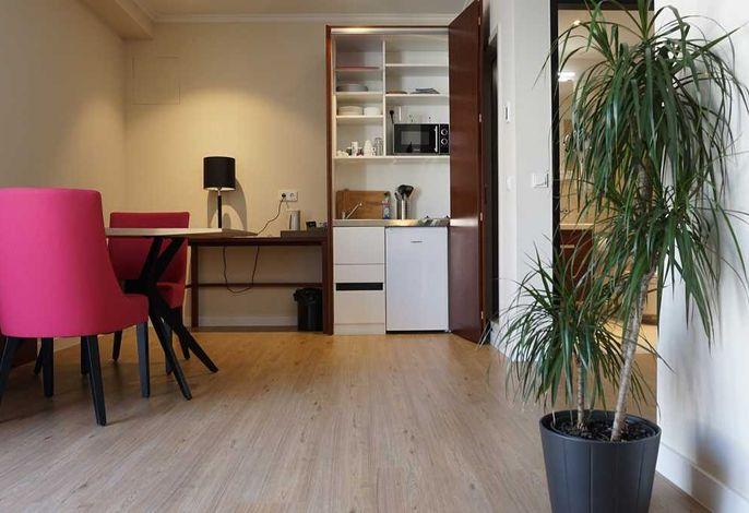 Wohnzimmer mit kleinem Essbereich und Miniküche