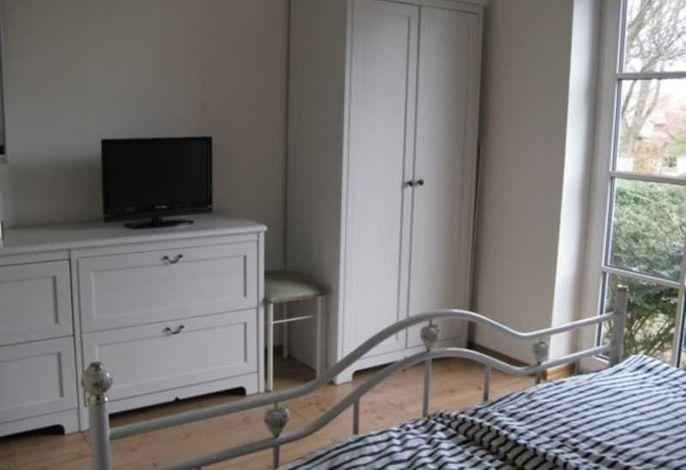 Schlafzimmer mit Doppelbett und zusätzlichem Flachbild-TV