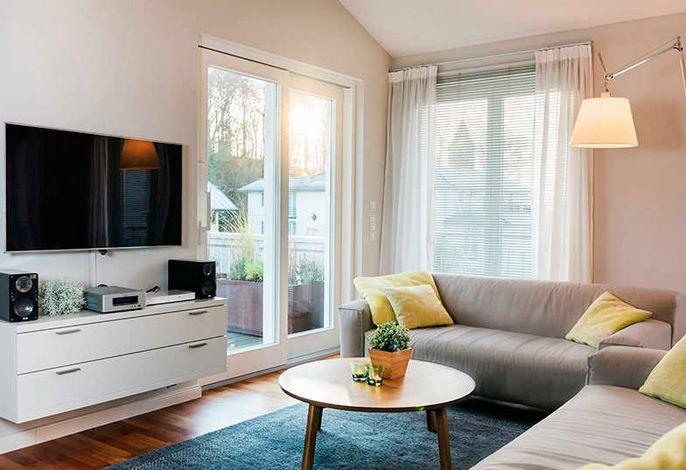 heller und moderner Wohnbereich mit Rolf Benz Sofa und TV