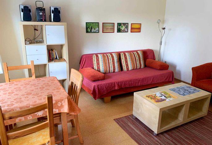 Wohnraum mit Schlafcouch und Esstisch